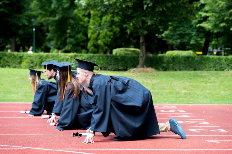 Groupe d'obtention du diplôme d'étudiants célébrant sur la voie sportive, préparation photographie stock libre de droits