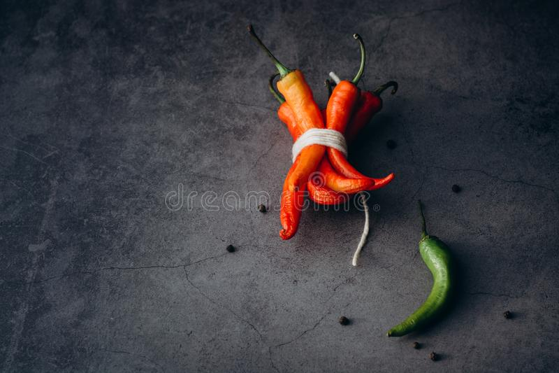 Groupe d'un rouge ardent de poivre de piments de piments, attaché par la ficelle sur un fond gris image libre de droits