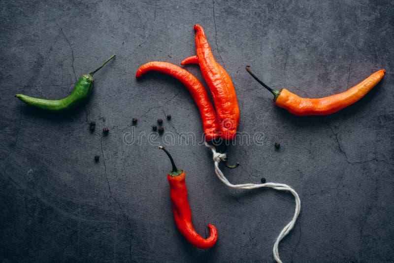 Groupe d'un rouge ardent de poivre de piments de piments, attaché par la ficelle sur un fond gris images stock