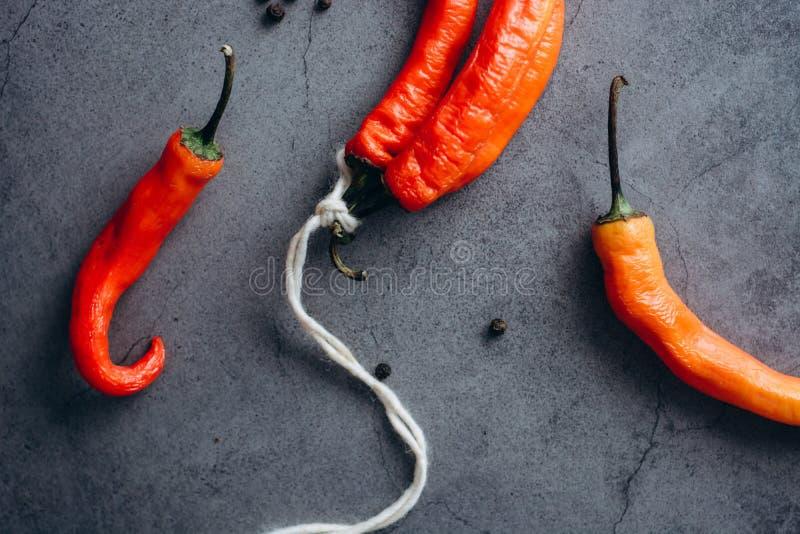 Groupe d'un rouge ardent de poivre de piments de piments, attaché par la ficelle sur un fond gris photos stock