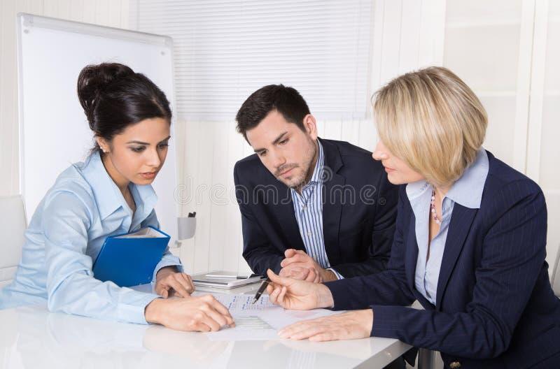 Groupe d'une équipe professionnelle d'affaires s'asseyant au talki de table photos libres de droits