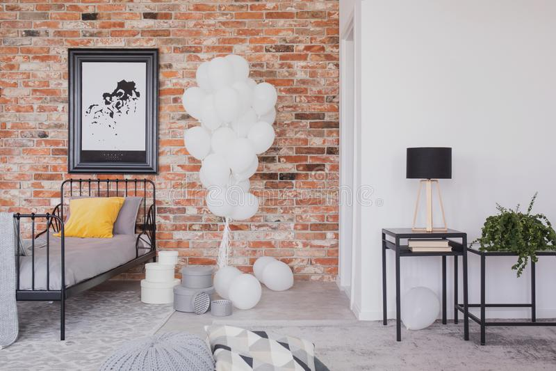 Groupe de ballons blancs à côté de lit noir simple en métal avec la literie grise et d'oreiller jaune dans la chambre à coucher i photo stock