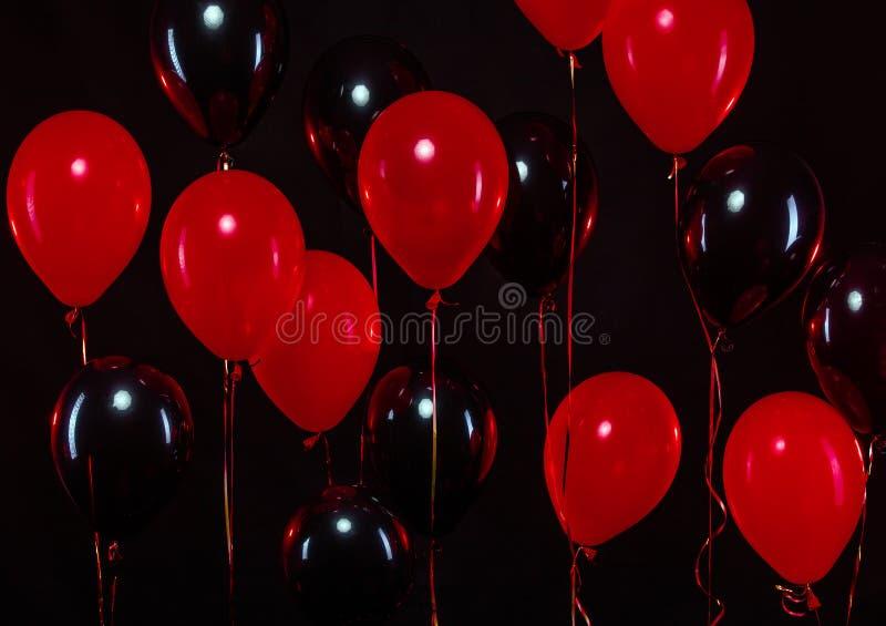 Groupe de ballons colorés sur le fond Noir et rouge images libres de droits