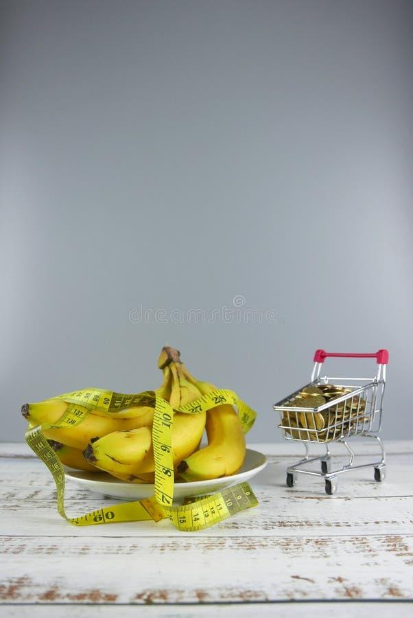 Groupe de bananes, de bande de mesure et de caddie complètement des pièces de monnaie sur le fond en bois Copiez l'espace pour le photos stock