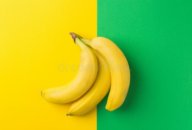 Groupe de bananes mûres sur le fond vert jaune de duotone Configuration plate à la mode créative Consommation propre de nourritur photographie stock