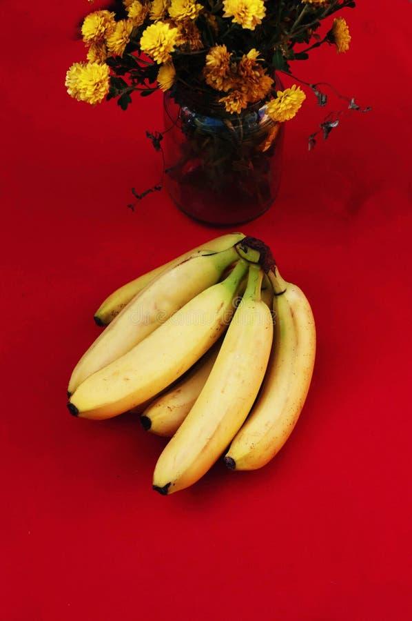 Groupe de bananes sur le fond rouge Banane organique fraîche, bananes fraîches sur la table de cuisine photo stock