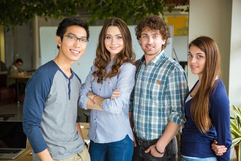 Groupe de beaux étudiants sûrs satisfaits de sourire se tenant ensemble photos libres de droits