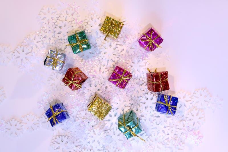 Groupe de boîte-cadeau colorés lumineux sur le fond artificiel blanc de flocons de neige photographie stock libre de droits
