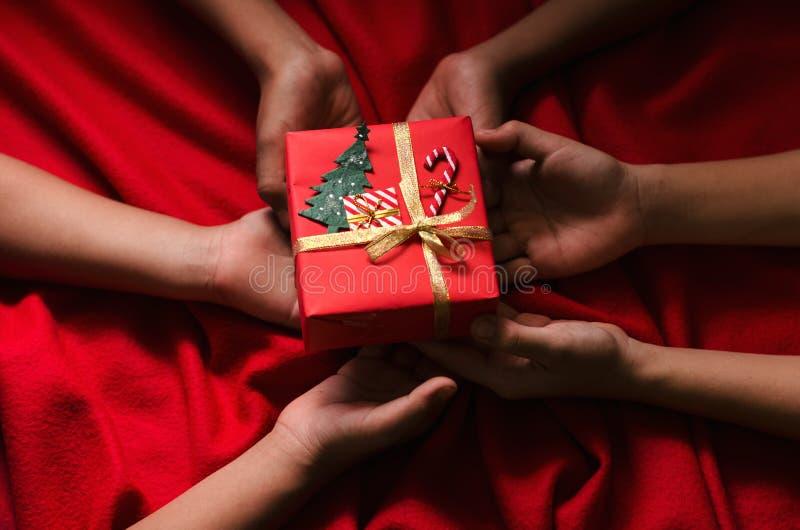 Groupe de boîte-cadeau de Noël de prise d'enfants de main sur le fond rouge images stock