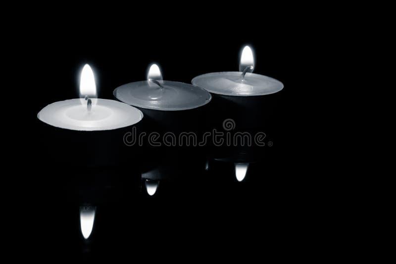 Rangée de trois bougies, en noir et blanc images stock