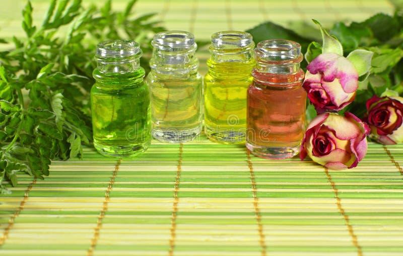 Groupe de bouteilles avec des herbes et des roses image stock