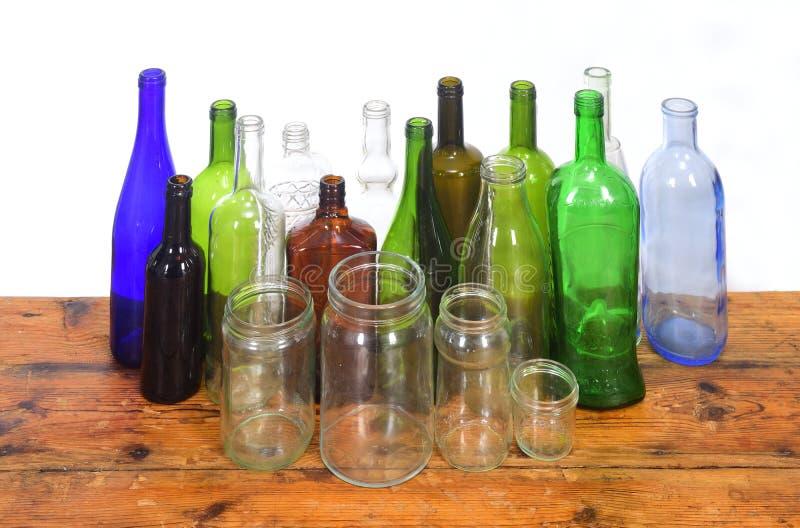 Groupe de bouteilles et de pots en verre sur une table en bois avec le fond blanc image stock