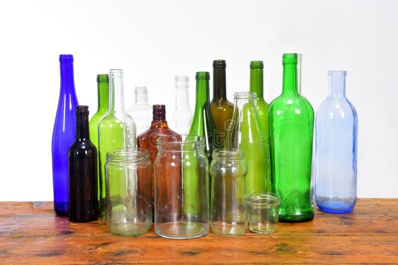 Groupe de bouteilles et de pots en verre sur une table en bois avec le fond blanc photographie stock
