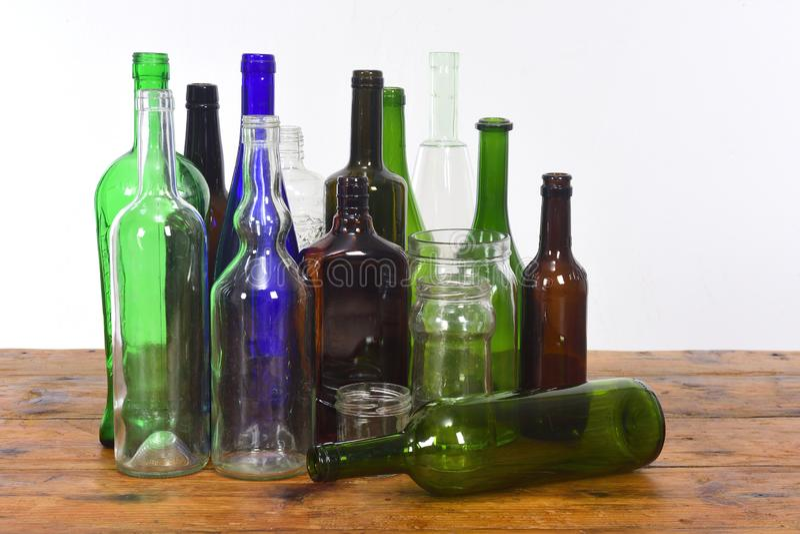 Groupe de bouteilles et de pots en verre sur une table en bois avec le fond blanc photos stock