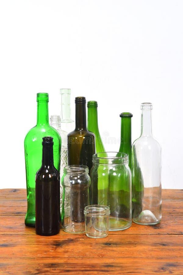 Groupe de bouteilles et de pots en verre sur une table en bois avec le fond blanc photo stock