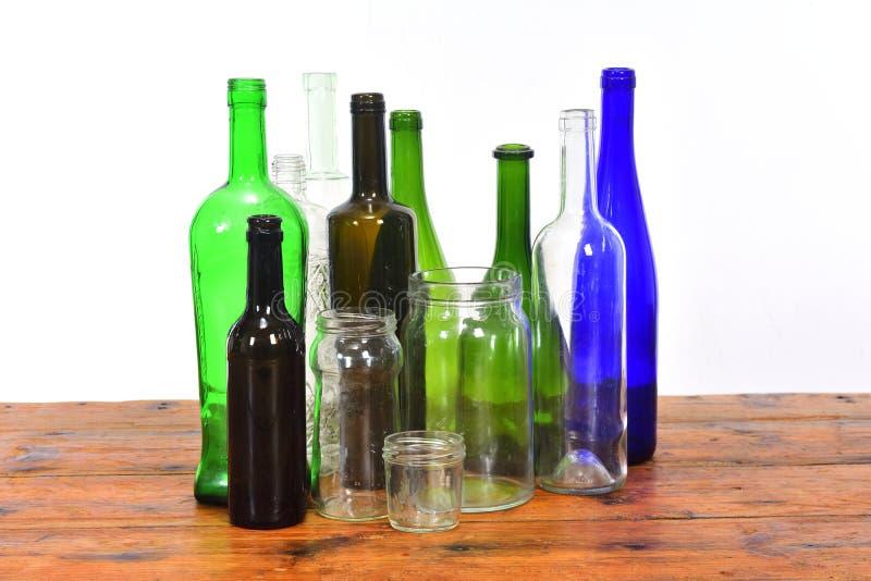 Groupe de bouteilles et de pots en verre sur une table en bois avec le fond blanc images libres de droits