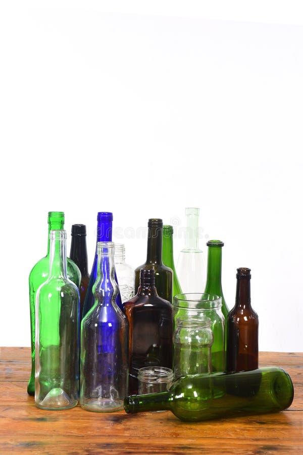 Groupe de bouteilles et de pots en verre sur une table en bois avec le fond blanc image libre de droits
