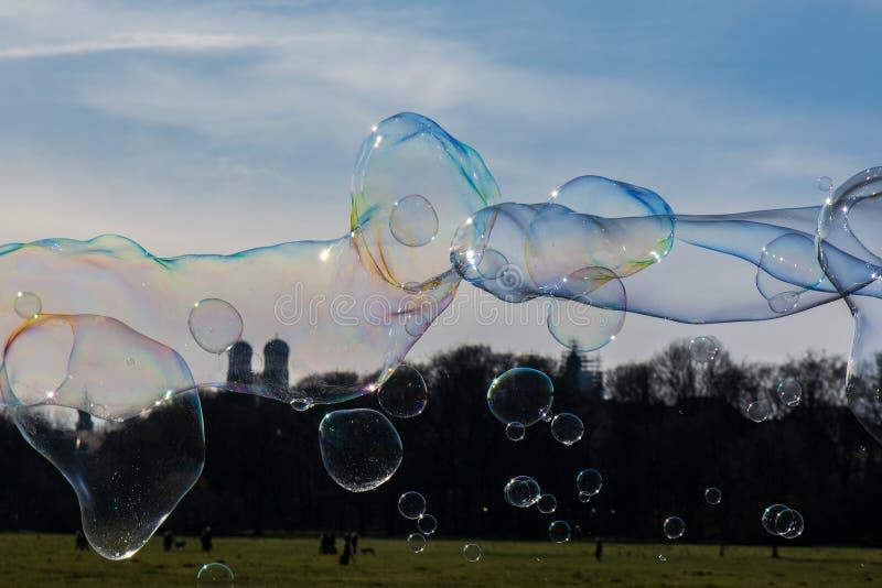 Groupe de bulles différemment classées flottant le dessus du paysage de Munich photos libres de droits