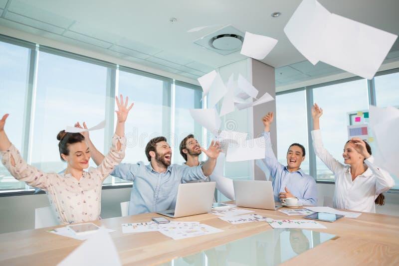 Groupe de cadres commerciaux célébrant en jetant leurs papiers d'affaires dans le ciel images stock