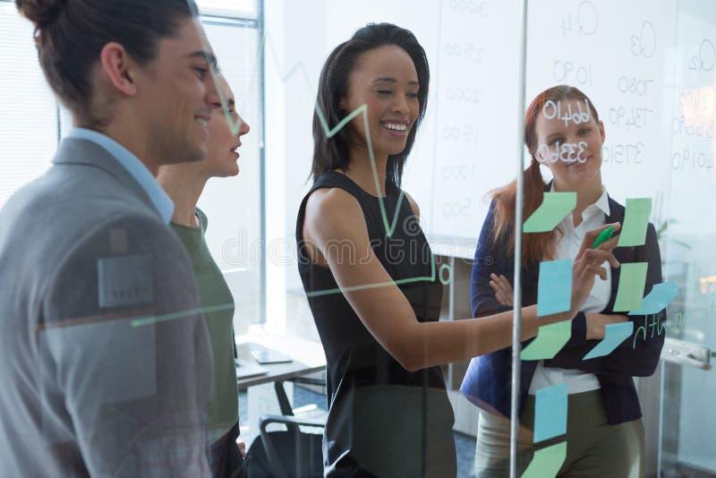 Groupe de cadres discutant au-dessus des notes collantes sur le mur au bureau images stock
