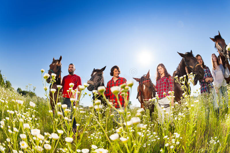 Groupe de cavaliers de horseback dans le pré fleuri photographie stock libre de droits