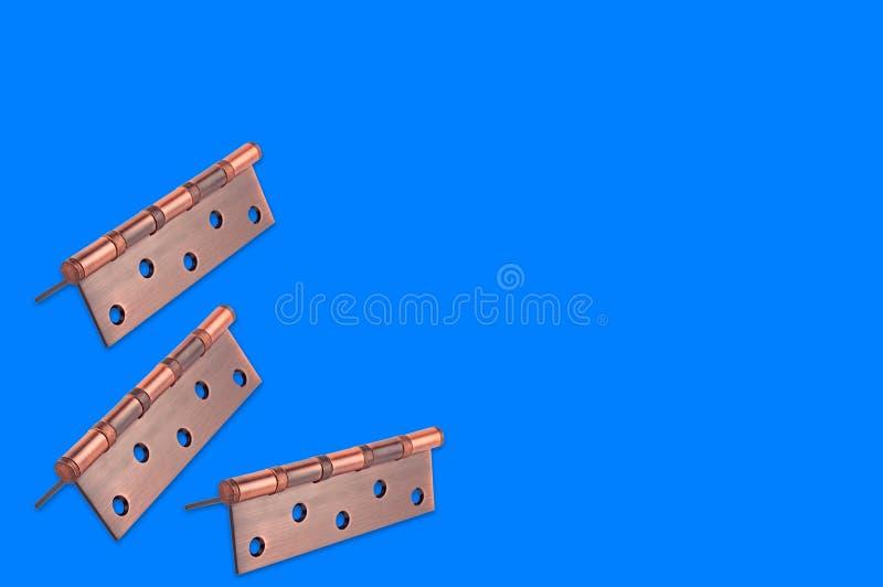 Groupe de charnières de porte brunes en métal sur le fond bleu images stock