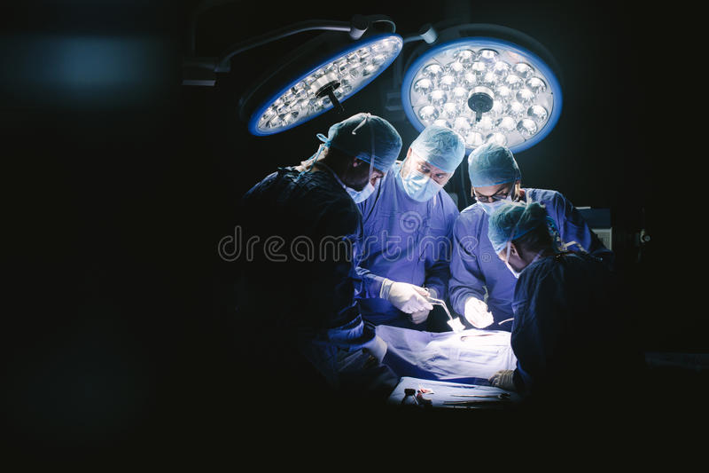 Groupe de chirurgiens dans le théâtre d'opération d'hôpital image stock