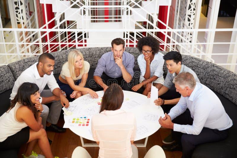 Groupe de collègues de travail ayant la réunion dans un lobby de bureau image stock