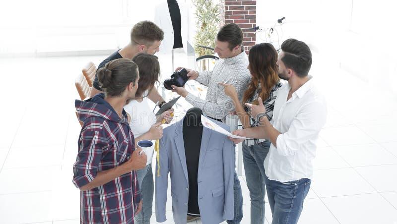 Groupe de concepteurs discutant de nouveaux modèles d'habillement du ` s des hommes image stock