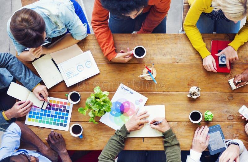 Groupe de concepteurs divers ayant une discussion photo stock