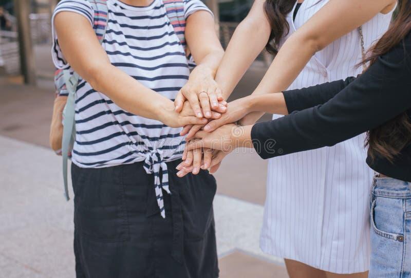 Groupe de coordination réussie de main d'université d'éducation de personnes de femme, étudiant mettant leurs mains photos stock