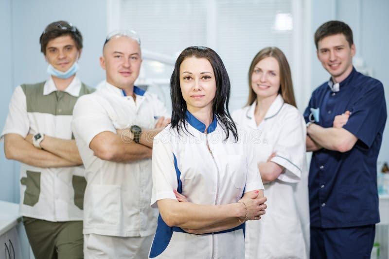 Groupe de dentistes se tenant dans leur bureau et regardant l'appareil-photo images libres de droits