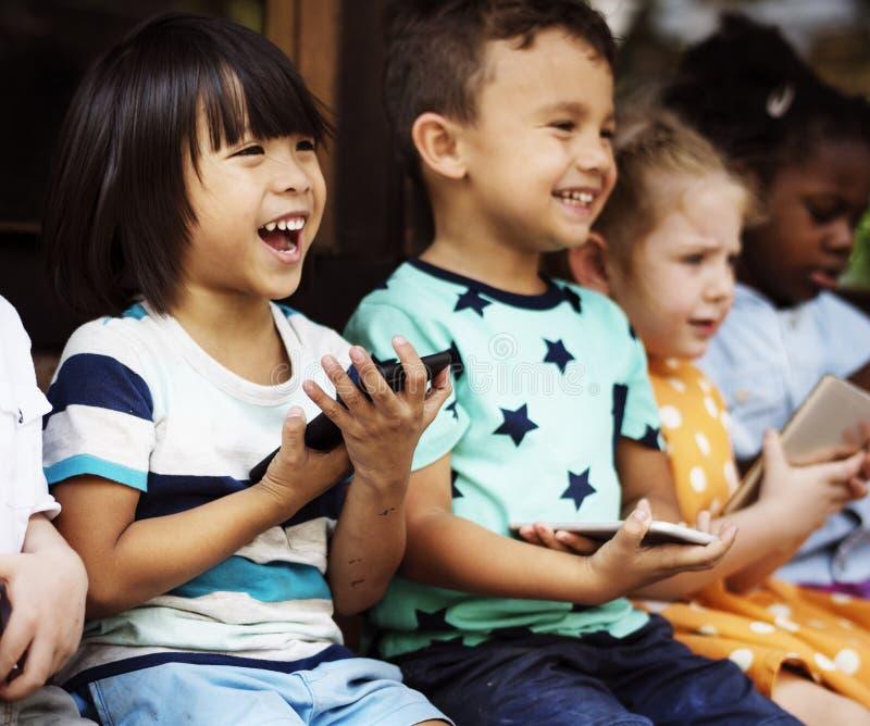 Groupe de diversité d'enfants jouant le téléphone photos stock