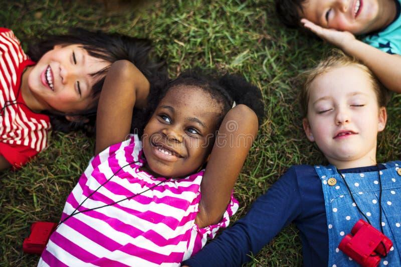 Groupe de diversité d'enfants se trouvant sur l'herbe photos stock