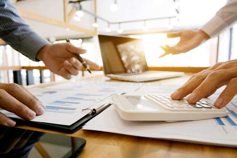 Groupe de document et de calcul de données d'analyse de cadres commerciaux au sujet de l'impôt d'honoraires à un bureau image stock