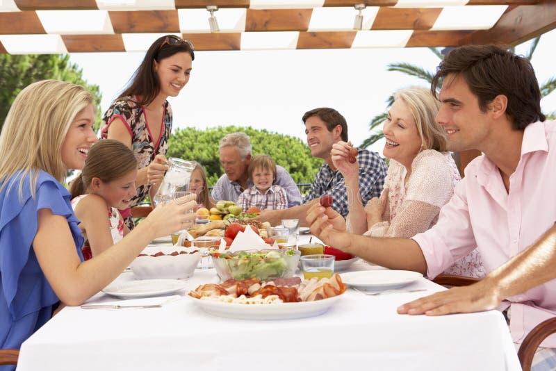 Groupe de famille étendu appréciant le repas extérieur ensemble photographie stock