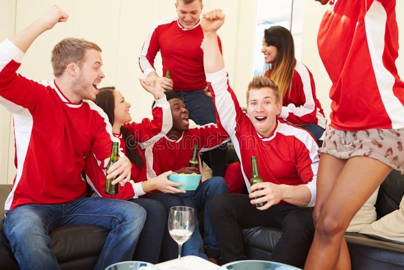 Groupe de fans de sports observant le jeu à la TV à la maison images stock
