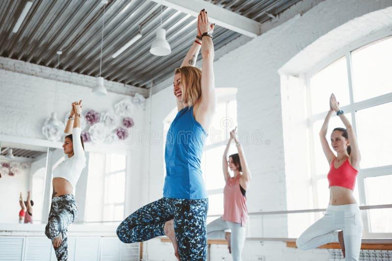 Groupe de femme en bonne santé s'exerçant ensemble et faisant l'exercice convenable dans le gymnase blanc Le yoga de pratique en  photos stock