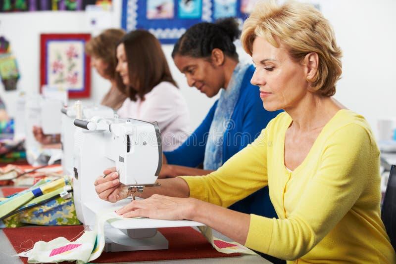 Groupe de femmes à l'aide des machines à coudre électriques dans la classe photographie stock libre de droits