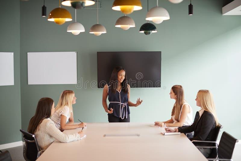 Groupe de femmes d'affaires s'asseyant autour du Tableau de salle de réunion et collaborant sur la tâche au jour licencié d'évalu photo stock