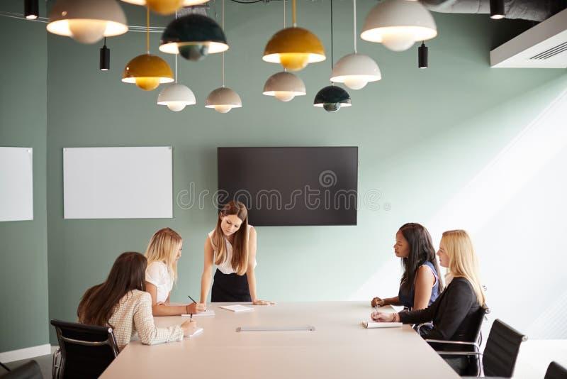 Groupe de femmes d'affaires s'asseyant autour du Tableau de salle de réunion et collaborant sur la tâche au jour licencié d'évalu image libre de droits