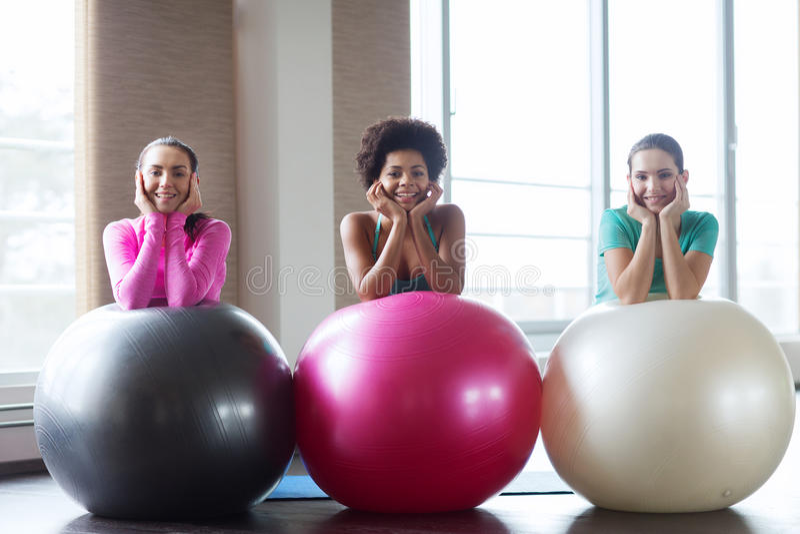 Groupe de femmes de sourire avec des boules d'exercice dans le gymnase photographie stock libre de droits