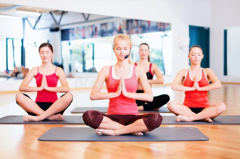 Groupe de femmes de sourire méditant dans la pose de yoga image libre de droits