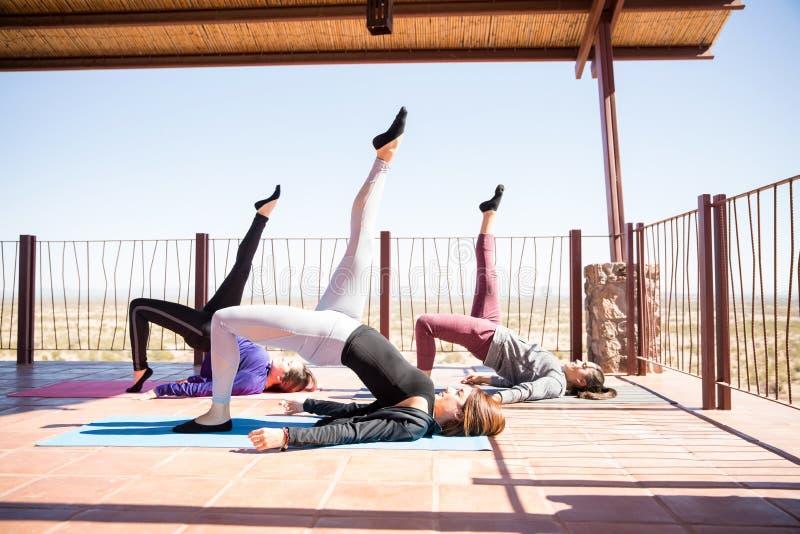 Groupe de femmes faisant une pose de pont en jambe photos libres de droits