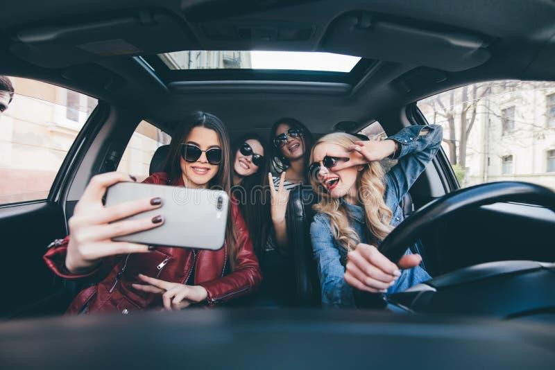Groupe de filles ayant l'amusement dans la voiture et prenant des selfies avec l'appareil-photo sur le voyage par la route images libres de droits