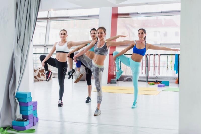 Groupe de filles caucasiennes minces se tenant dans la position d'un-jambe pendant la classe de séance d'entraînement dans le gym photographie stock libre de droits