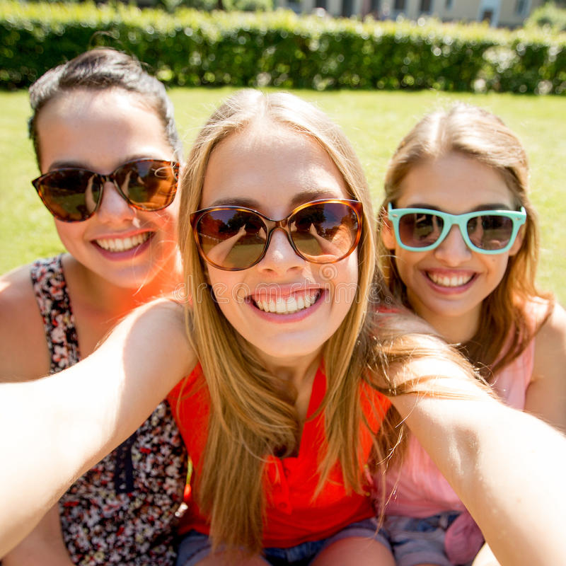Groupe de filles de l'adolescence de sourire prenant le selfie en parc photographie stock libre de droits
