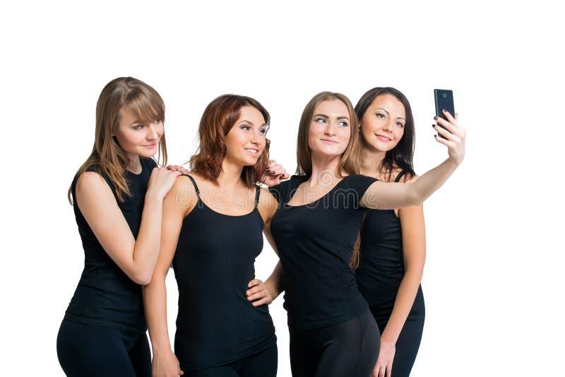 Groupe de filles faisant le selfi d'isolement au blanc photo stock