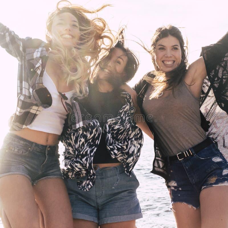 Groupe de filles gaies et heureuses sautant avec bonheur et appréciant l'amitié et le youthness loisir ext?rieur pour photos libres de droits