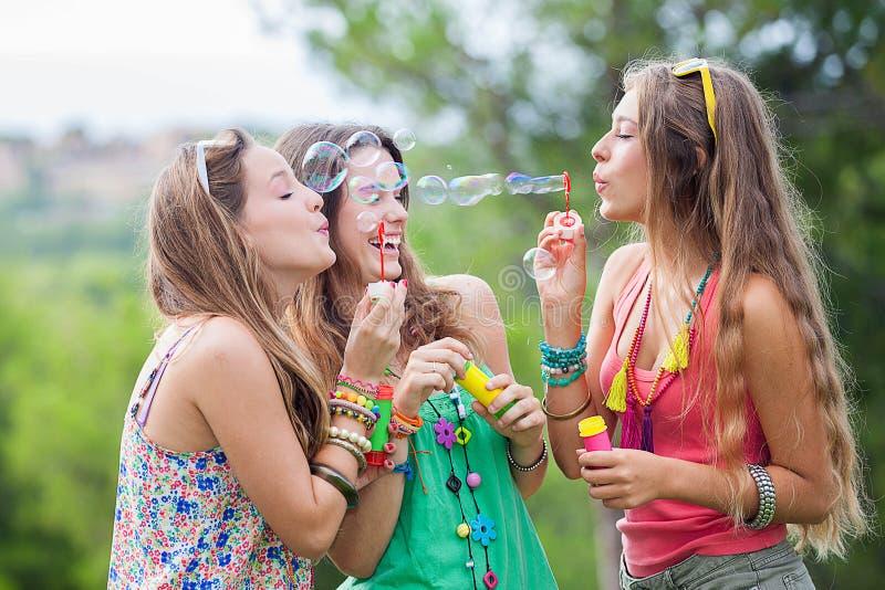 Groupe de filles soufflant des bulles au festival de musique images stock
